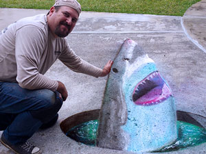 Posing with 3D chalk art of shark in a hole in the ground