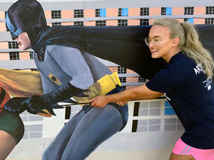 Batman & Robin mural with girl posing