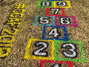 Spray chalk hopscotch game on grass