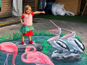 Child posing on Everglades pond with pelicans and flamingos 3D pavement art