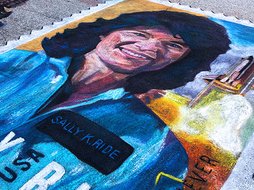 Posing with Sally Ride stamp pavement chalk art side view