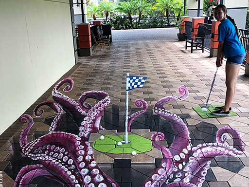 Posing with golf putting green with octopus tentacles 3D pavement art