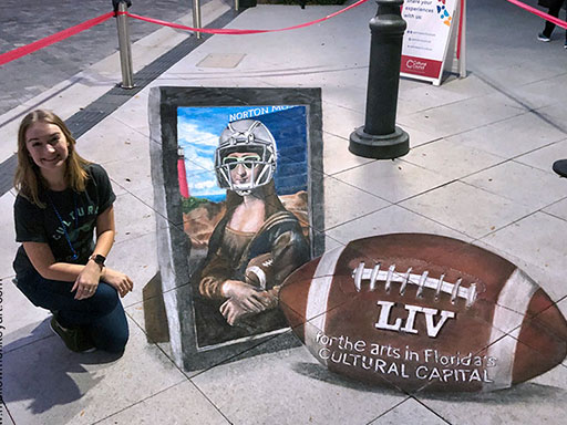 Posing with 3D Mona Lisa in a football helmet chalk art
