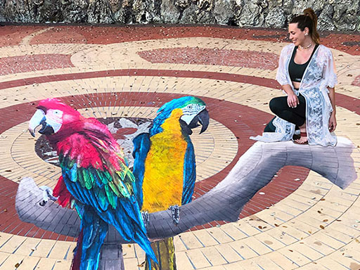 Posing with 3D macaws chalk art